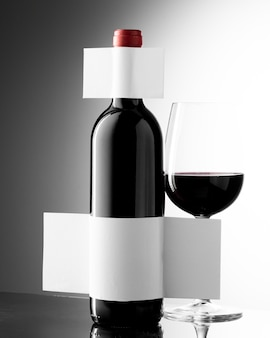 Vista frontal da taça de vinho com garrafa e rótulo em branco