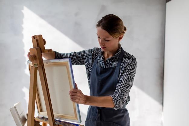 Vista frontal da tela do artista em estúdio