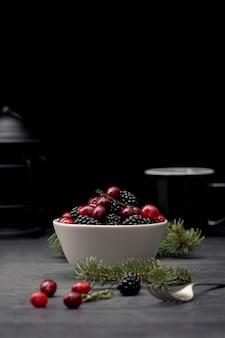 Vista frontal da tigela com cranberries e amoras