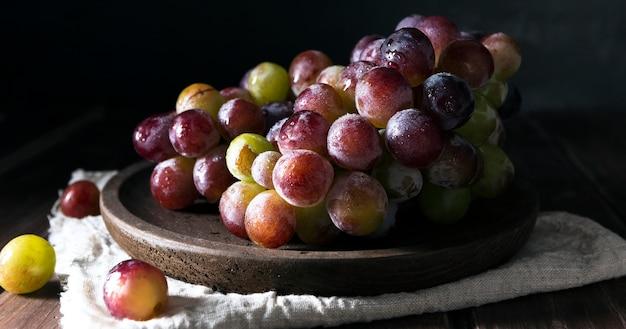 Vista frontal da tigela com uvas de outono