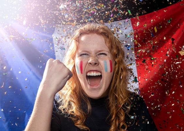Vista frontal da torcida mulher com a bandeira francesa e confetes