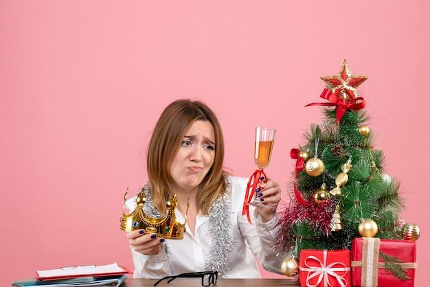 Vista frontal da trabalhadora com coroa e champanhe em rosa.