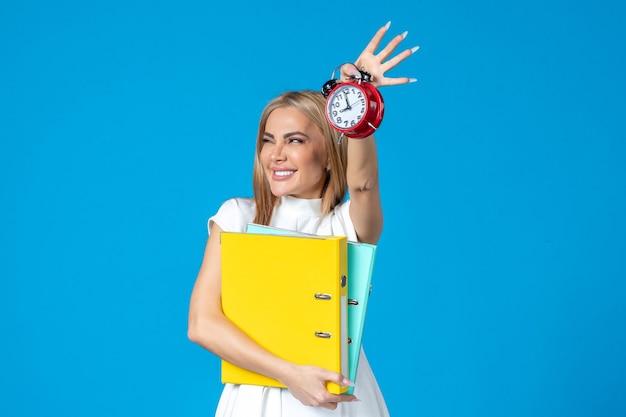Vista frontal da trabalhadora segurando a pasta e o relógio na parede azul