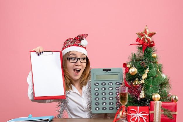 Vista frontal da trabalhadora segurando calculadora e nota de arquivo rosa