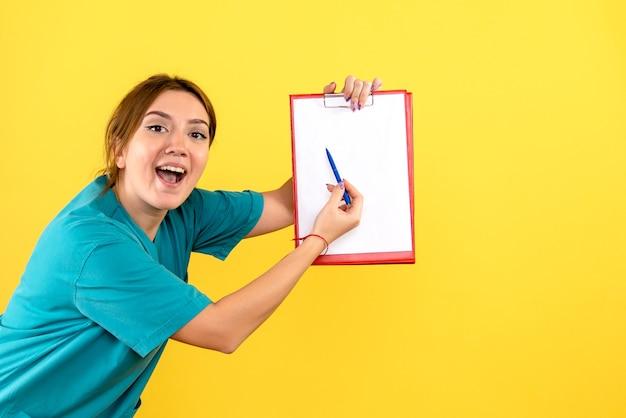 Vista frontal da veterinária segurando análises na parede amarela