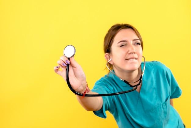 Vista frontal da veterinária usando estetoscópio na parede amarela