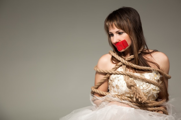 Vista frontal da vítima do sexo feminino com boca de fita adesiva, olhando para baixo.