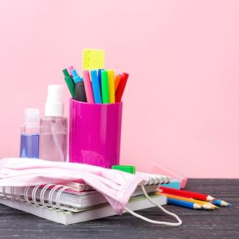 Vista frontal da volta aos artigos de papelaria da escola com lápis e máscara médica