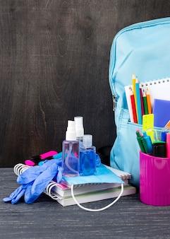 Vista frontal da volta aos artigos de papelaria da escola com mochila e lápis