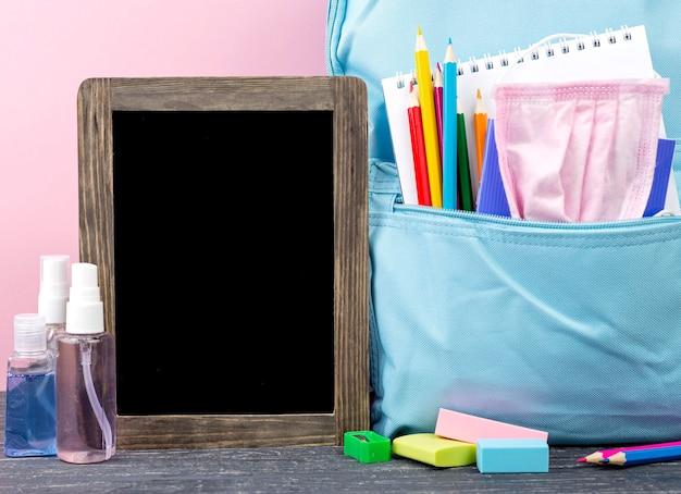 Vista frontal da volta aos artigos de papelaria da escola com mochila e quadro-negro