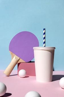 Vista frontal das bolas de pingue-pongue, raquete e copo de papel