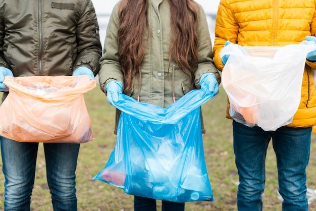 Vista frontal das crianças com sacos de plástico