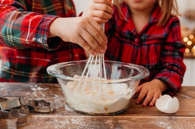 Vista frontal das crianças fazendo biscoitos de natal