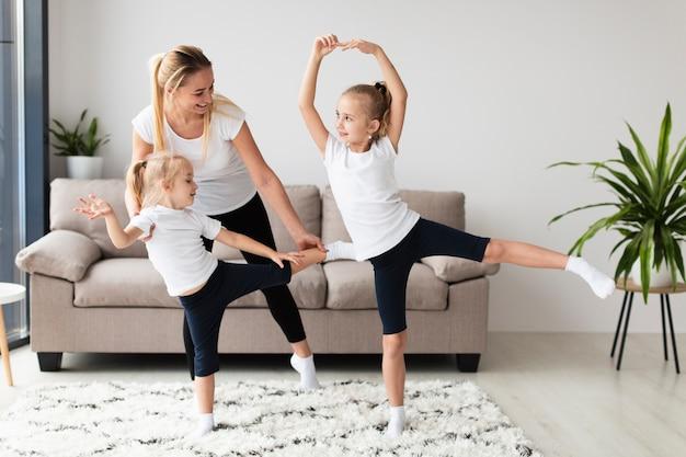 Vista frontal das filhas malhando com a mãe em casa