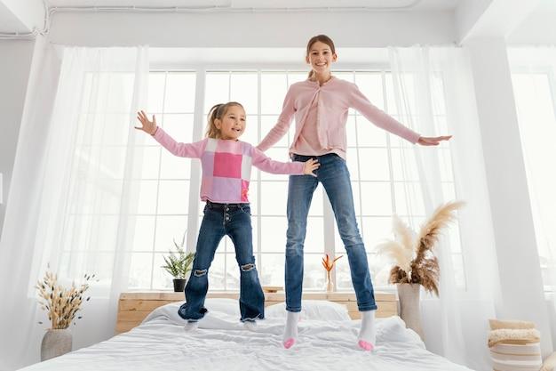 Vista frontal das irmãzinhas pulando na cama juntas