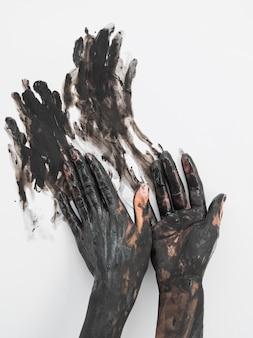 Vista frontal das mãos cobertas de tinta preta