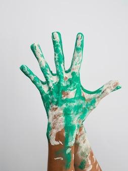 Vista frontal das mãos coloridas com tinta