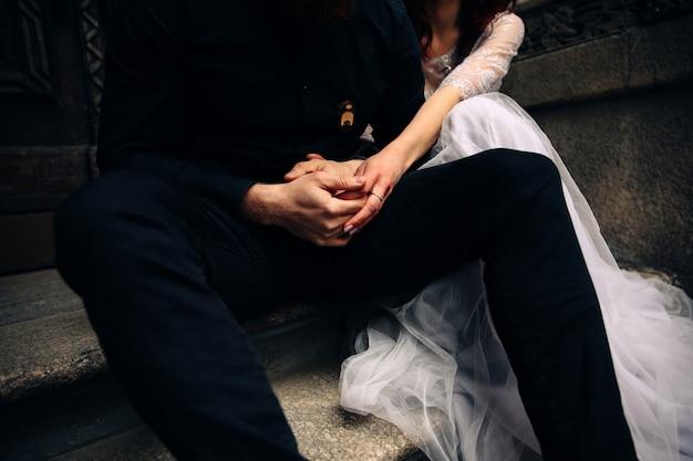 Vista frontal das mãos cruzadas do casal que está sentado na escada de pedra vestida em trajes de casamento