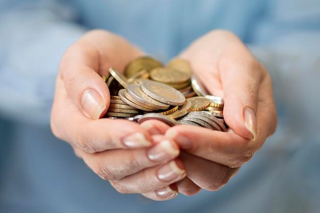 Vista frontal das mãos hodling moedas