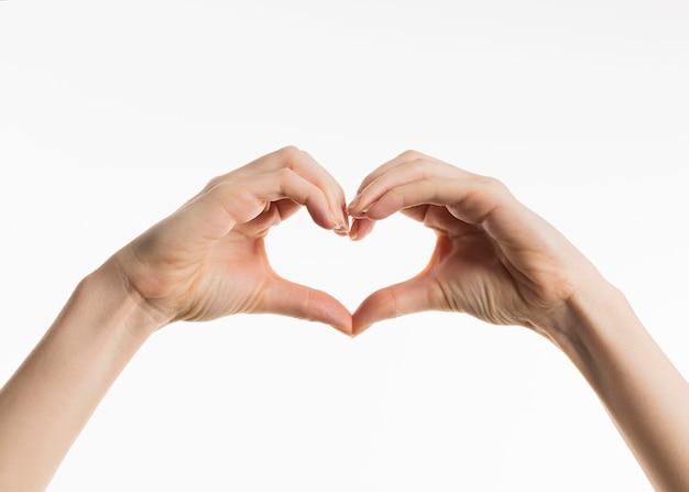 Vista frontal das mãos mostrando o sinal do coração