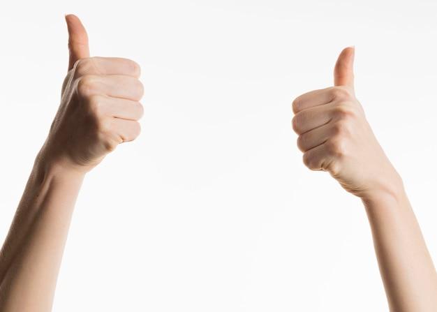 Vista frontal das mãos mostrando os polegares para cima