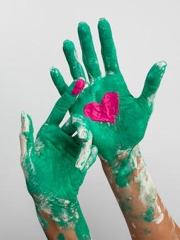 Vista frontal das mãos pintadas com coração