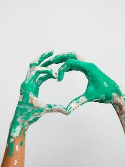 Vista frontal das mãos pintadas fazendo coração
