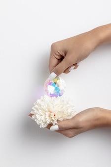 Vista frontal das mãos segurando flores e diamante