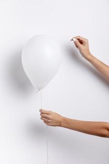 Vista frontal das mãos segurando um balão com agulha
