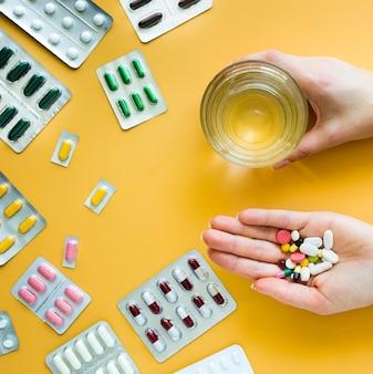Vista frontal das mãos segurando um copo de água e vários comprimidos