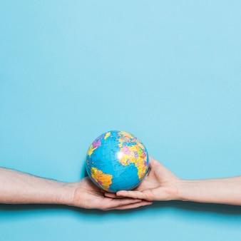 Vista frontal das mãos segurando um globo com espaço de cópia