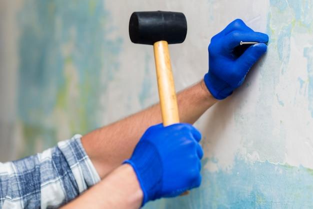 Vista frontal das mãos segurando um martelo