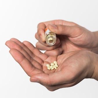 Vista frontal das mãos segurando um monte de pílulas