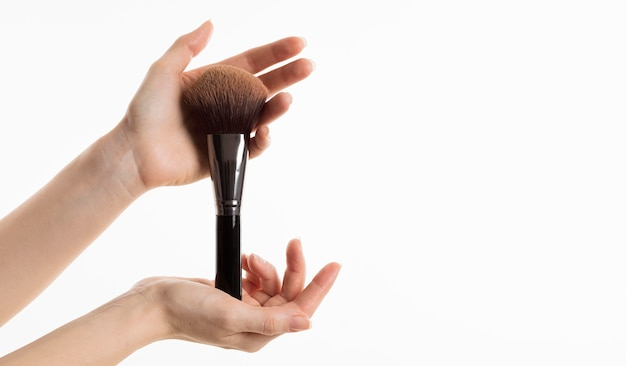 Vista frontal das mãos segurando um pincel de maquiagem
