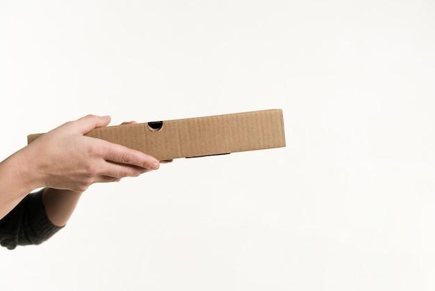 Vista frontal das mãos segurando uma caixa de pizza