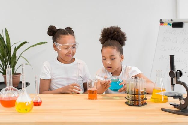 Vista frontal das meninas experimentando química em casa