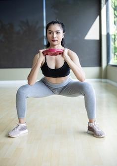 Vista frontal das mulheres em uniformes esportivos, fingindo agachar e segurar halteres em pé no ginásio.