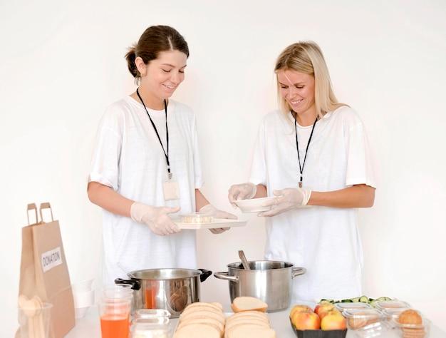Vista frontal das mulheres preparando comida para doação