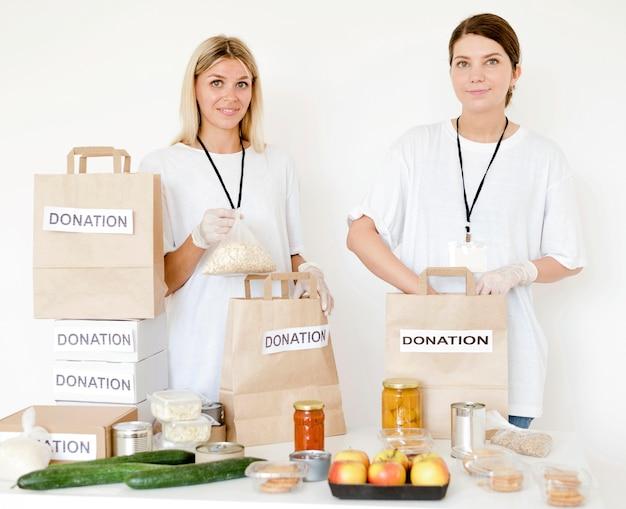 Vista frontal das mulheres preparando sacos de doação de alimentos