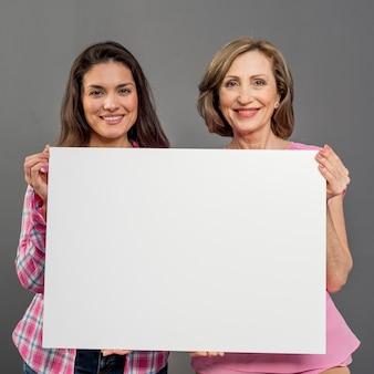 Vista frontal das mulheres segurando a folha de papel em branco