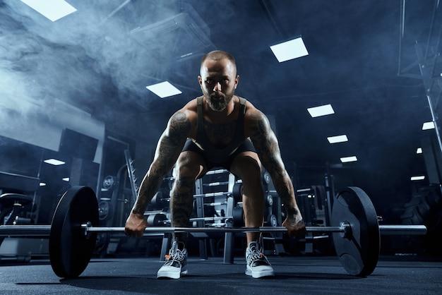 Vista frontal das pernas de treinamento de fisiculturista barbudo com barra.
