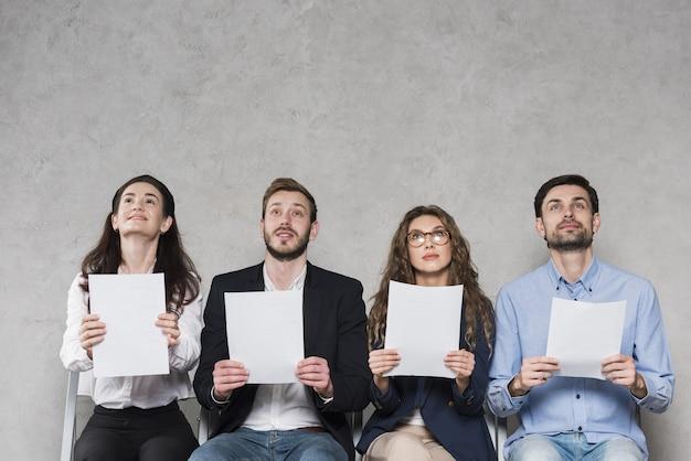 Vista frontal das pessoas à espera de suas entrevistas de emprego segurando papéis em branco, com espaço de cópia