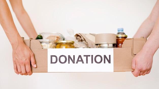 Vista frontal das pessoas segurando a caixa de doações com comida