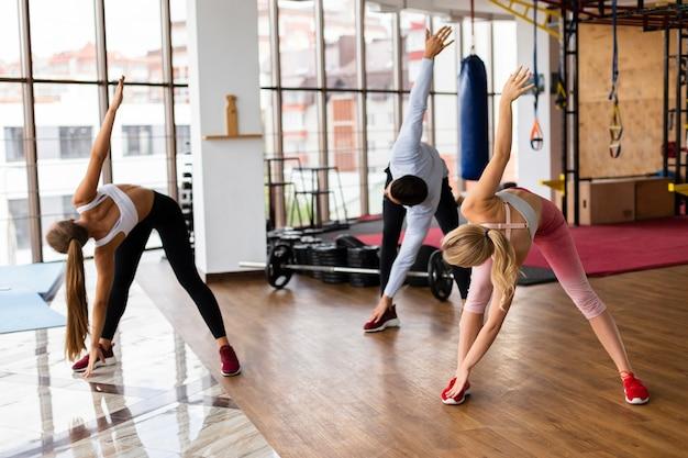 Vista frontal das pessoas treinando na academia
