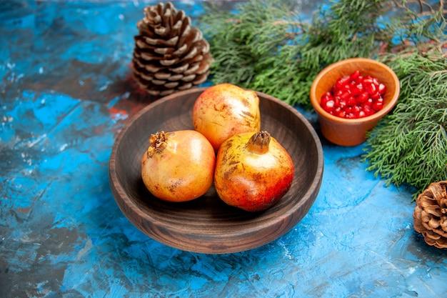 Vista frontal das romãs em uma placa de madeira. sementes de romã em uma tigela de madeira galho de árvore de pinho e cones em azul
