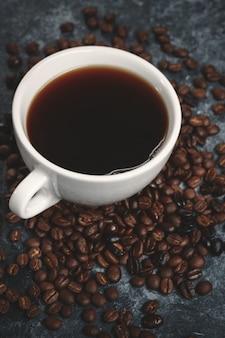 Vista frontal das sementes de café com uma xícara de café na superfície escura