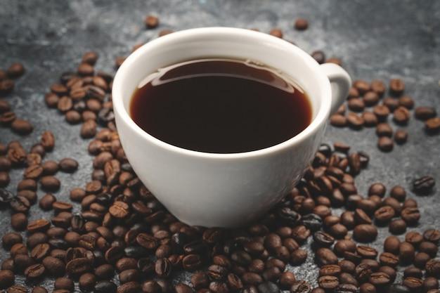 Vista frontal das sementes de café marrom com uma xícara de café na superfície escura