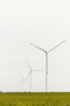 Vista frontal das turbinas eólicas no campo com espaço de cópia