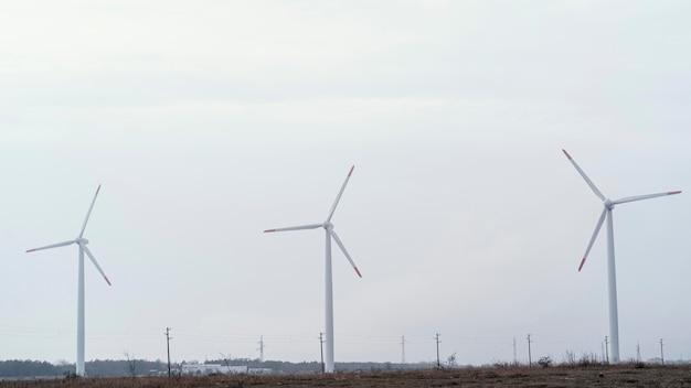 Vista frontal das turbinas eólicas no campo gerando energia elétrica