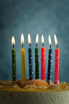 Vista frontal das velas de aniversário multicoloridas acesas
